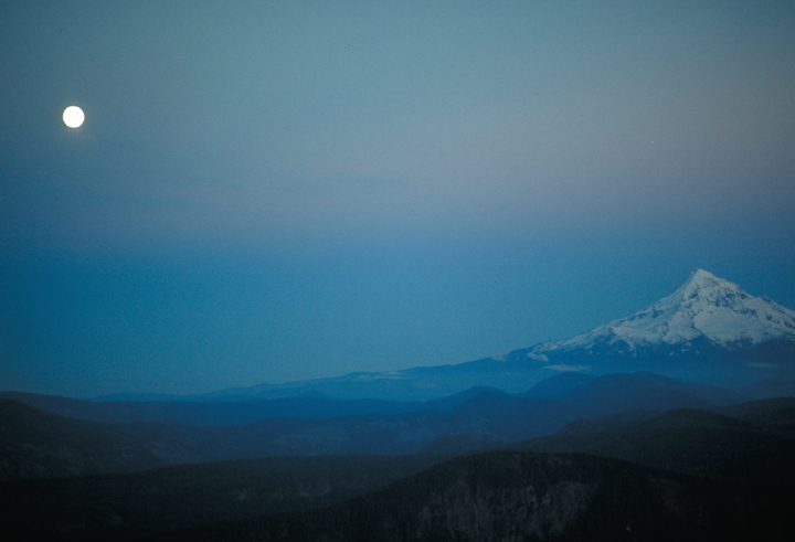 The moon drifts lazily across the sky, casting a chilly light on the single snowy peak below just after sunset.